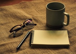 Top view of writer objects concept: notebook, pen, eyes glasses and cup of coffee on sack cloth in retro filter effect