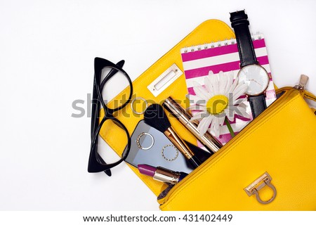 Top view of yellow bag with make up female fashion accessories. Stylish glasses, watch , lipstick , notebook , mascara , smart phone