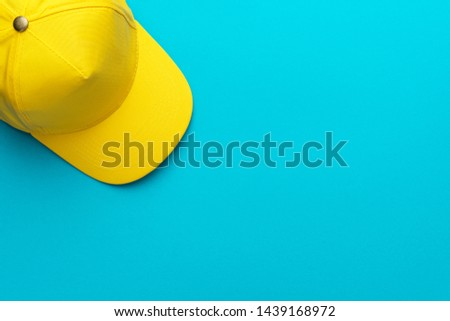 Top view of yellow baseball cap over the blue torquoise background. Flat lay mock-up image of unisex bright yellow cap. Photo of yellow baseball hat with copy space.