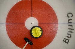 Top view of yellow curling stone in inner red ring of the house, near the button, with broom nearby.