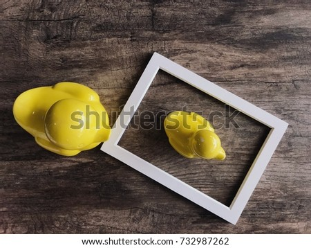 Top view of yellow ducky family in blank picture frame on aged grunge wood floor texture , copy space for creative