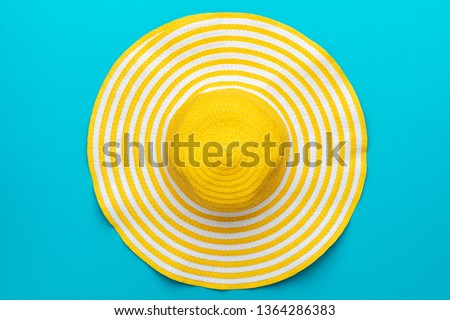 top view of yellow hat close-up over blue background. minimalist photo of striped retro hat summer concept #1364286383