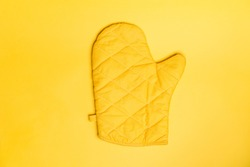 Top view of yellow oven gloves on yellow color background. Mockup for food banner and kitchen protection equipment.