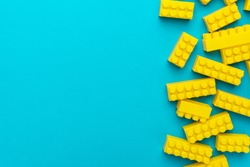 Top view of yellow plastic blocks. Right side composition of yellow building blocks from child constructor. Bright plastic blocks on torquoise blue background with copy space.