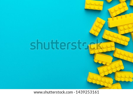 Top view of yellow plastic blocks. Right side composition of yellow building blocks from child constructor. Bright plastic blocks on torquoise blue background with copy space. stock photo