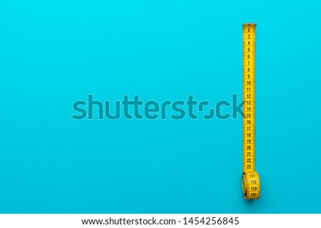 Top view of yellow soft measuring tape. Minimalist flat lay image of tape measure with metric scale over turquoise blue background. Right side composition photo of tape measure with copy space.