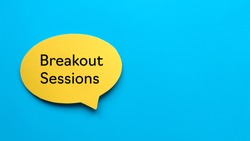 Top view of yellow speech bubble written with Breakout Sessions on blue background with copy space.