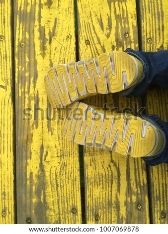 Stock Photo Top view of yellow sport shoes sneakers on a bright yellow wooden pathway