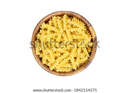 Top view of yellow uncooked fusilli pasta in round wooden bowl isolated on white background Foto d'archivio ©
