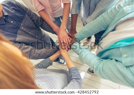 Top view of young business people of different nationalities holding hands together, cropped