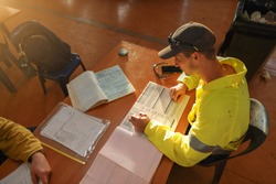 Top view of young construction gold miner worker seating writing job hazards analysis on hot work, working at height risk assessment safety control permit prior to start each shift