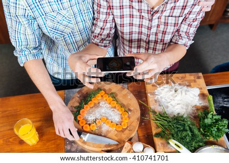 Top view of young couple making heart with cutted carrots and taking pictures with smartphone on the kitchen