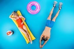 top view of young couple resting with beach items on blue, summer vacation concept