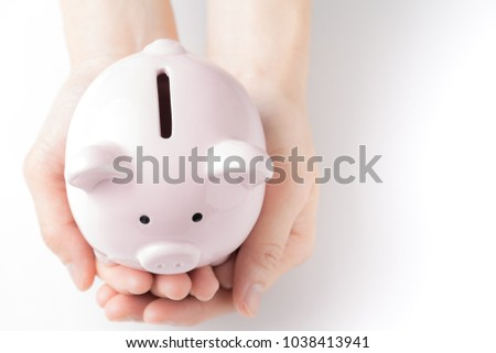 Top view of young female hands tender holding pink piggy bank on white table in soft tone, savings and invest for future growth. #1038413941