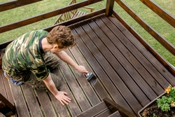 Top view of young man staining garden terrace wooden boards outdoors in spring. Terrace wood stain concept.