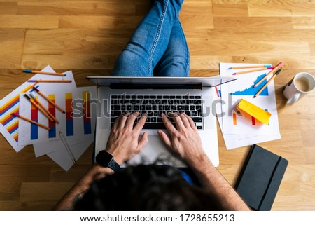 Top view of Young man working with his laptop from his living room. Stay at home, work from home concept