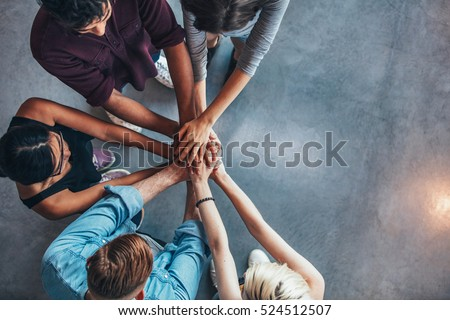 Top view of young people putting their hands on top of each other. Young students making a stack of hands with copy space.