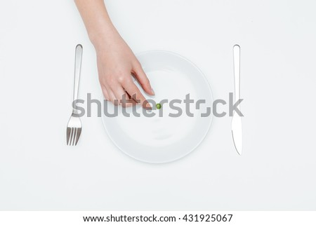 Top view of young woman hand taking one green pea from the plate over white background