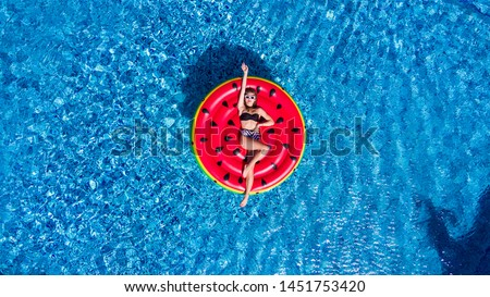 Top view of young woman relaxing on watermelon lilo in villa resort pool - Rich girl floating with fruit mattress drinking tropical cocktail - Summer holiday, luxury lifestyle and fashion concept