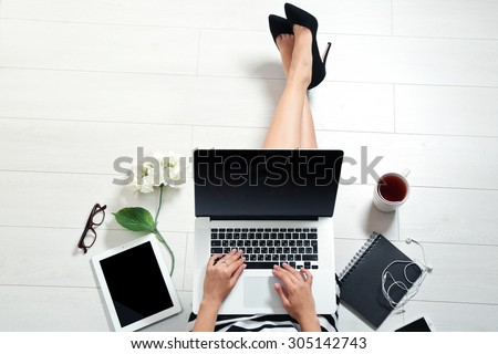 Top view of young woman sitting on floor with laptop #305142743