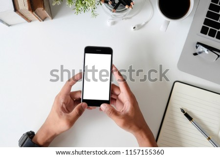 Top view office desk with mockup smartphone on hands with empty display screen. #1157155360