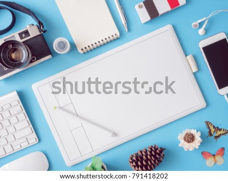 top view office desk workspace with smartphone, notebook, graphic tablet, pantone books, keyboard and retro camera film on blue background, graphic designer, Creative Designer concept