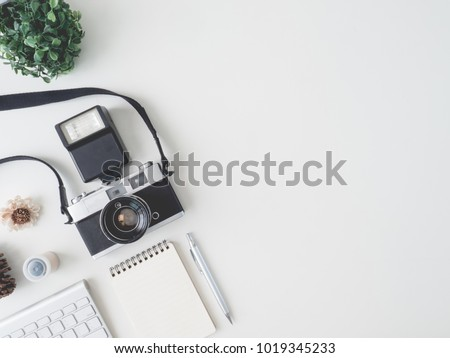 top view office table concept with retro camera, notebook and keyboard on white Color table background with copy space