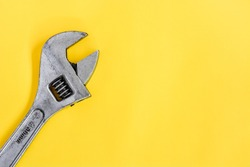 top view old adjustable wrench isolated yellow background, copy space