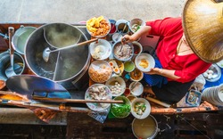 Top view old woman cooking Thai noodle soup Tom Yam style on Thai tradition boat in local floating market, Famous traditional Thai street food for tourist people travel Bangkok Thailand, Tasty Asia