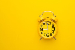 Top view old yellow alarm clock on bright color background