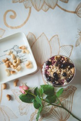 Top view on a bowl of organic cottage cheese yogurt with granola and black currant, a garden rose and a plate with cashew nuts on the table. Healthy eating concept. Toning