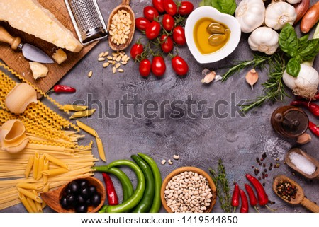 top view, on a dark rustic background, raw pasta and traditional Italian ingredients with olive oil, parmesan, vegetables, legumes and various types of spices