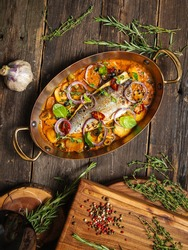 Top view on a delicious dish of home-made seabass fillet with mushrooms and potatoes in a saucepan in a pan on a wooden table, vertical format