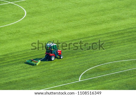 Top view on a tractor cares for the football field #1108516349
