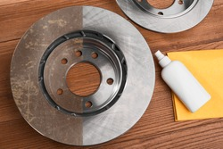 Top view on an anti-rust spray with a cloth and a brake disc. Half-cleaned rotor, before and after treatment.