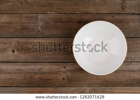 Top view on an empty soup plate on rustic wooden table. Classic dishware, clean and simple look for a tabletop. #1282071628
