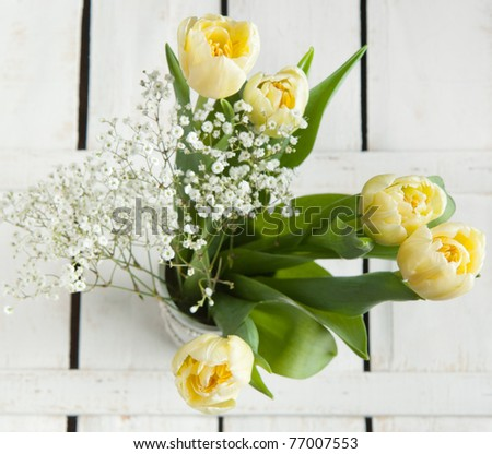 Top view on bouquet of yellow tulips and little white flowers on white wooden table