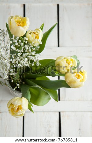 Top view on bouquet of yellow tulips on white wooden table