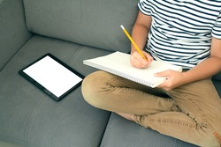 Top view on boy writing or drawing and using his tablet while doing homework. Studying online during quarantine, online training classes or personal education plan concept. Back to school. Mockup