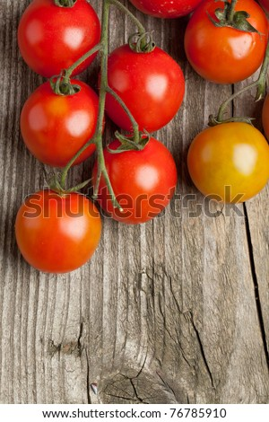 Top view on branch of fresh cherry tomatoes on old wooden background
