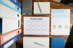 Top view on calendar for ideas and tasks for 2020. Table with documentation containing statistics. Calculator for business audit and accounting of profits and expenses of company