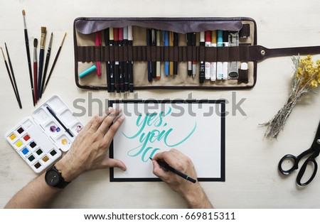 Top view on calligrapher hands writing words Yes, you can with blue marker on blank paper on wooden table background with markers in leather case, dried yellow flowers,brushes and watercolor palette.  #669815311