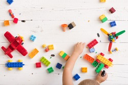 Top view on child playing and building with colorful plastic bricks at white wooden table. Early learning and development.