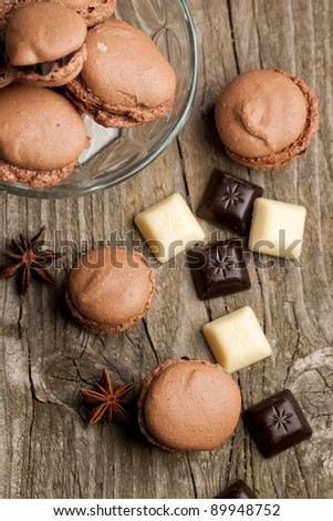 Top view on chocolate macaroons with pieces of white and black chocolate on old wooden table
