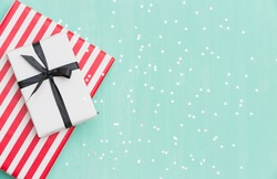 Top view on Christmas gifts wrapped in striped gift paper decorated with ribbon on turquoise wooden background with sparkling stars. New Year, holidays and celebration concept