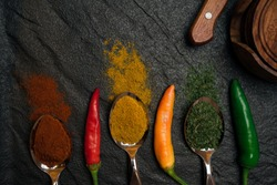 Top view on colorful oriental spices in spoons and scattered and red green yellow peppers on the black metallic tray in Asian style
