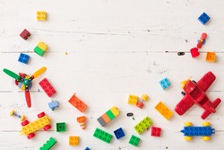 Top view on colorful plastic toy bricks and details on white wooden background