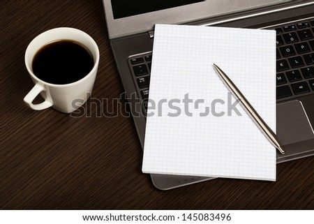 Top view on dark wooden office desk with laptop, sheet of paper, pen and cup of coffee.