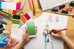 Top view on fashion designer at work. Female hands drawing clothes sketch at her creative workspace and using smartphone with green gradient color swatches on screen, top view