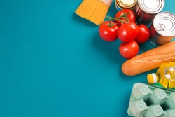 Top view on food donations on green background with copyspace - pasta, fresh vegetables, canned food, baguette, eggs, organic oil. Donation, volunteering or contactless delivery food concept. Flat lay